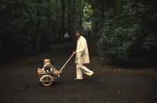 2006-47-030 Diareportage van het Holland Popfestival in het Kralingse Bos (30): een man loopt met een kind in een ...