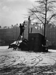 XXXIV-21-00-01-04 Een lantaarnopsteker, die een straatlantaarn schoonmaakt op de Wolfshoek. Op de achtergrond ...