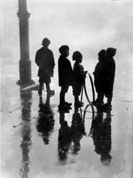 XXXIV-29-01-02-12 Kinderen in de regen bij de Zeevischmarkt. De jongen tweede van rechts heeft een hoepel in zijn hand.