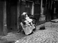 XXXIV-29-01-02-3 Gezicht op een grootmoeder met klein kind op schoot in een steeg.
