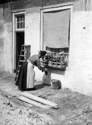 XXXIV-29-01-02-7 Een huisvrouw die bezig is met de was aan het ophangen.