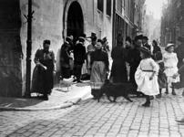 XXXIV-30-1 Gezicht op oude vrouwtjes, kinderen komend uit de Sint Sebastiaanskapel, ook wel Schotse kerk genoemd, aan ...