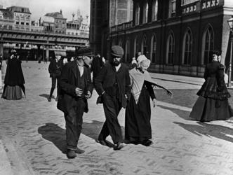 XXXIV-30-10 Gezicht op mensen bij de Grote Kerk aan het Grotekerkplein, op de achtergrond het spoorwegviaduct aan de ...