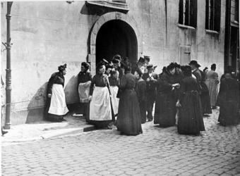 XXXIV-30-2 Gezicht op oude vrouwtjes, mannen komend uit de Schotse kerk aan de Lombardstraat.