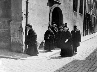 XXXIV-30-4 Gezicht op oude vrouwtjes, mannen komend uit de Sint Sebastiaanskapel ook wel Schotse kerk genoemd aan de ...