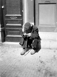 XXXIV-30-5 Gezicht op een oude bedelaar op de stoep voor een huisdeur aan de Mauritsweg.