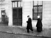 XXXIV-30-7 Gezicht op een echtpaar uit het Armehuis, voor het gebouw de Doelen