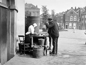 XXXIV-33-2 Een mosselenverkoopster bij de Oostpoort, aan het Oostplein.