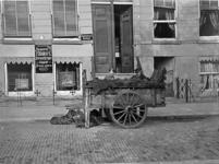 XXXIV-34-1 Gezicht op turfkar met straatverkoopster en verkoper bij het Bosje voor het atelier voor moderne fotografie ...