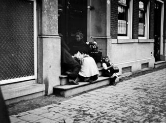 XXXIV-34-2 Gezicht op straatventers in een portiek van een huis aan de Mauritsweg.