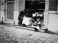 XXXIV-34-3 Gezicht op straatventers in een portiek van een huis aan de Mauritsweg.