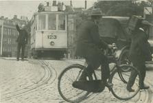 1969-1600 Een verkeersagent regelt het verkeer op het Hofplein.Op de achtergrond de Stationsweg.
