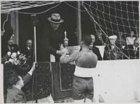 1976-14253 De koning van Noorwegen (Haakon VII) reikt een beker uit aan de aanvoerder van een voetbalelftal op het veld ...