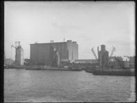 1976-4038 Elevatoren in de Maashaven nabij het betonnen gebouw van de NV Graansilo Maatschappij, de Maassilo.