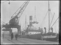 1976-4287 Het lossen van een zeeschip met sinaasappelen aan een kade met hijskranen van de IJsselhaven.
