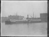1976-4466 Het schip Amata met hout in de Rijnhaven, op de achtergrond de vemen van NV Handelsveem Rotterdam en NV ...