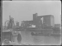 1976-4572 Op de voorgrond de Maashaven met overslag via graanelevatoren en schepen. Op de achtergrond de Maassilo.