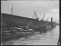 1976-4672 Langs de kade van de Spoorweghaven staan goederenwagons en schepen liggen aangemeerd aan de kade.
