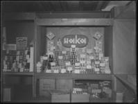 1976-4787 Levensmiddelen van de HAKA coöperatie staan uitgestald met een verwijzing erbij naar het eerst ...