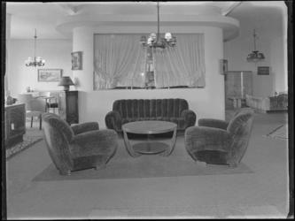 1976-4947 Interieur van een woonkamer met bankstel en salontafel in een meubelzaak.
