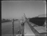 1976-5047 De Spoorweghaven. Langs de kade staan goederenwagons en een vrachtschip ligt aangemeerd langszij.