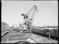 1976-5175 Kranen van de firma Van Dam & Co aan de Prins Hendrikkade. Rechts op de achtergrond het Poortgebouw en links ...