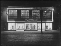 1976-5362 Het winkelbedrijf van Lampe aan de Nieuwe Binnenweg 36, met de verlichte etalage's bij avond.