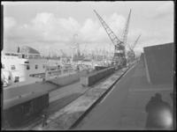 1976-5597 Schepen in de Merwehaven, aangemeerd langs de kade(n), hijskranen bij het goederenemplacement.