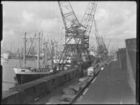 1976-5598 Schepen in de Merwehaven, aangemeerd langs de kade(n), hijskranen bij het goederenemplacement.