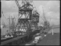 1976-5600 Schepen in de Merwehaven, aangemeerd langs de kade(n), hijskranen bij het goederenemplacement.