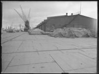 1976-5701 Het oostelijk havendeel van de Merwehaven. Goederen onder zeilen van de firma Bingham & co.