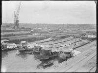1976-6157 Overzicht van de Merwehaven, op de voorgrond binnenvaartschepen met Binghamzeilen afgedekte lading.