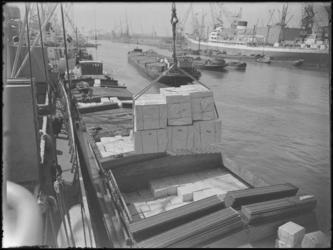 1976-6326 Laden en lossen. De overslag van stukgoederen in de Merwehaven vanuit een schip naar een binnenvaartschip.