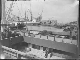 1976-6327 Overslag van stukgoederen in de Merwehaven. Het laden en lossen van goederen vanuit een het ruim van een ...