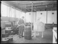 1976-6909 Personeelslid van het bedrijf Deluxol Olie maatschappij nv. vult een vat olie.