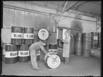 1976-6912 Een werkruimte van de expeditie van het bedrijf Deluxol Olie maatschappij nv. Twee personeelsleden bij de ...