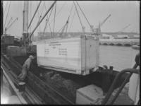 1976-7168 Kisten worden in het ruim van een schip geladen in de Binnenhaven.