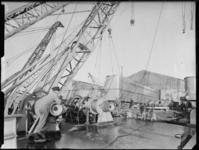 1976-7335 Een groot scheepsonderdeel wordt uit de loods getransporteerd.