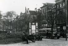 1976-7698 De Grotemarkt met een bus voor openbaar vervoer en een bord met het vertrektijdenrooster van de busdienst.
