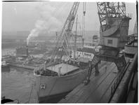 1976-7776 Het laden / lossen van zware stukken uit een schip met hulp van een drijvende bok in de Merwehaven.