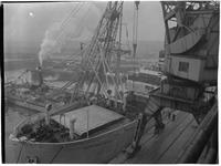 1976-7777 Het laden / lossen van zware stukken uit een schip met hulp van een drijvende bok in de Merwehaven.
