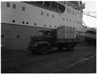 1976-7806 Aan de kade worden houten kisten met een kleine vrachtwagen aangevoerd of afgevoerd van een schip.