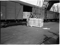 1976-7837 Overslag in de haven. Het laden / lossen van houten kisten in een treinwagon aan de kade.
