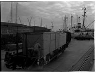 1976-7838 Overslag in de haven. Het laden / lossen van houten kisten in een treinwagon aan de kade.