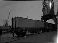 1976-7839 Overslag in de haven. Het laden / lossen van houten kisten in een treinwagon aan de kade.