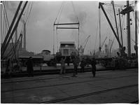 1976-7861 Het laden en lossen van vrachtwagens op de kade in de haven.
