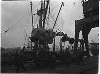 1976-7863 Het laden en lossen van een landbouwvoertuig op de kade in de haven.