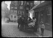 2008-5218 Een verkoper met handkar op de kruising van de Sint Laurensstraat en het Rodezand. De straat links is het ...