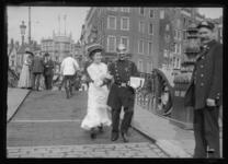 2008-5227 Een dame en een politieagent wandelen gearmd over de Roobrug.