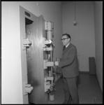 10054 G.S. de Vries, adjunct-directeur Stichting Spaarbank te Rotterdam, bij een geopende kluisdeur.